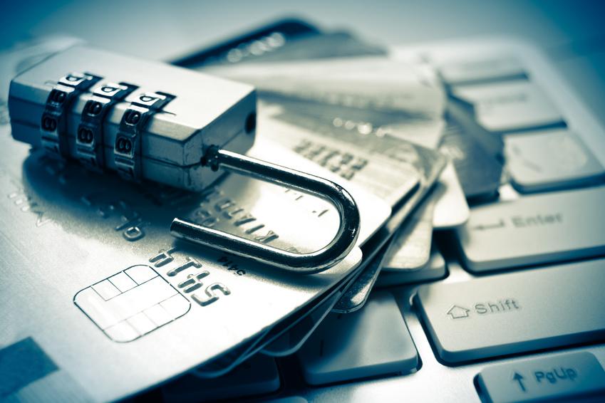 Candado con combinación y tarjetas de crédito simulando herramientas para evitar el fraude bancario
