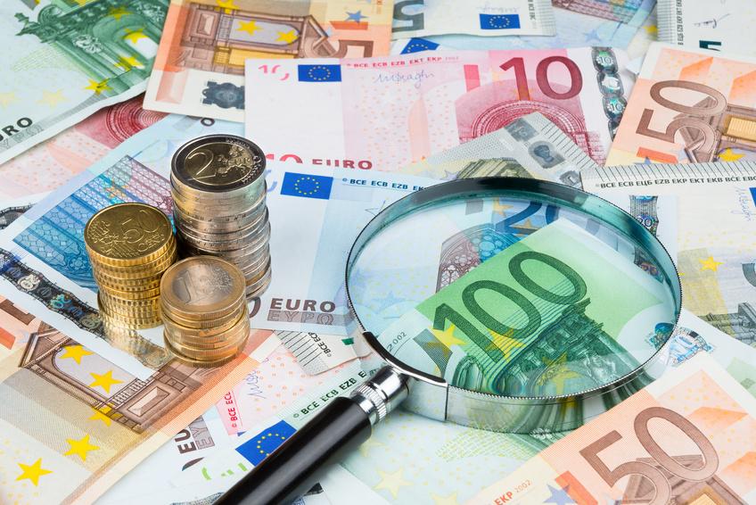 Billetes y monedas de euro con lupa que podría pertenecer a un grupo organizado de blanqueo de capitales