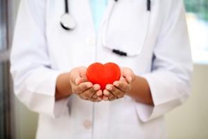 Imagen de un médico con un corazón ficticio en las manos informado sobre prevención de riesgos laborales cardíacos
