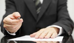 Hombre ofreciendo un bolígrafo para firmar un contrato, detrás de falsas ofertas existe blanqueo de capitales