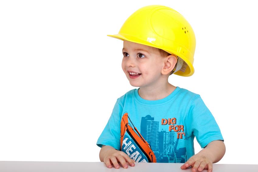 Niño con un casco amarillo recibiendo formación infantil sobre prevención de riesgos laborales