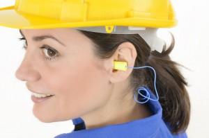 Mujer utilizando casco y tapones para los oídos, dos indispensables para la prevención de riesgos laborales