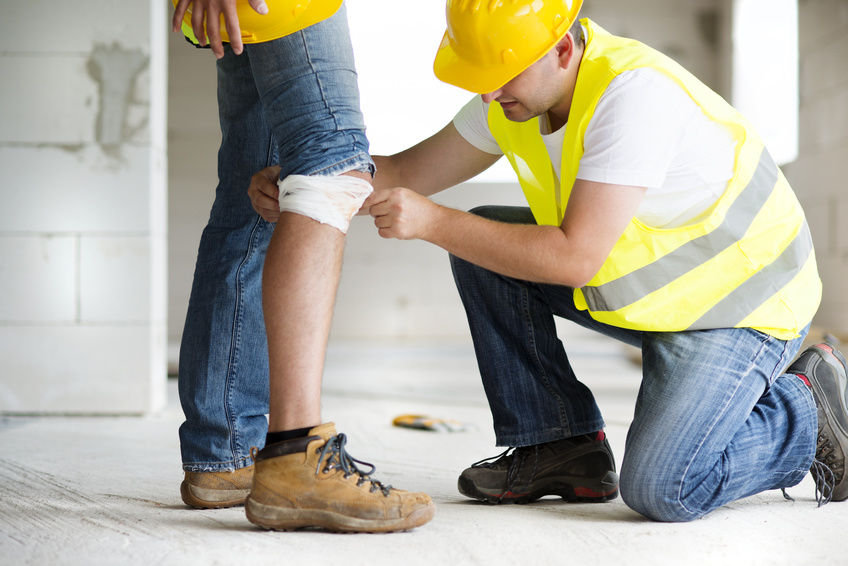 Un operario pone una protección a la rodilla de otro en una actuación de prevención de riesgos laborales