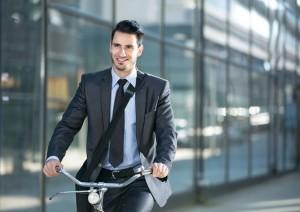 Hombre en bicicleta acudiendo a su sitio de trabajo donde tienen en cuenta la prevención de riesgos laborales