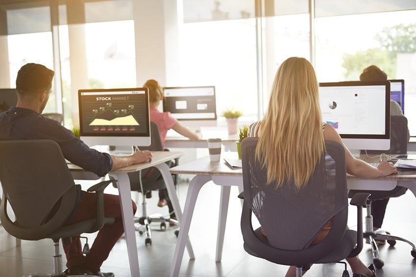 Personas trabajando en una postura correcta cuidando la ergonomía