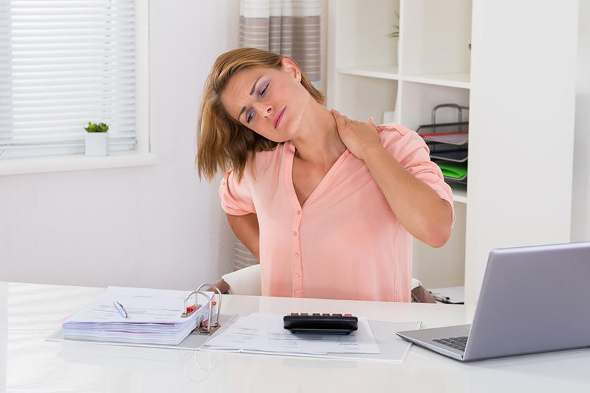 Mujer trabajando con una postura corporal incorrecta provocándole con dolor de espalda