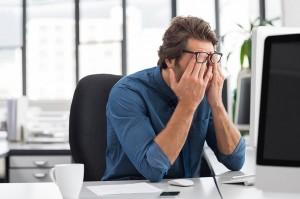 Hombre cansado delante de una pantalla de ordenador afectado por las TIC