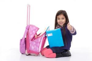 Niña con carrito escolar que es mejor es mejor a nivel postural para los niños que la mochila, para la prevención de riesgos en la salud