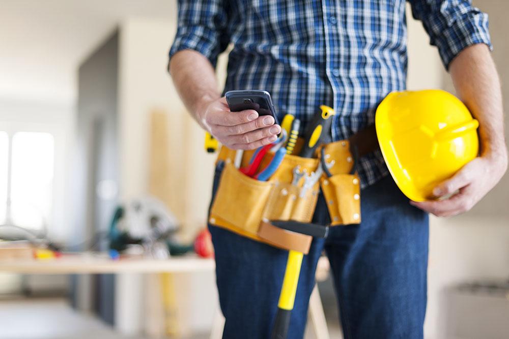 Un operario con un casco y un móvil velando por la prevención de riesgos laborales