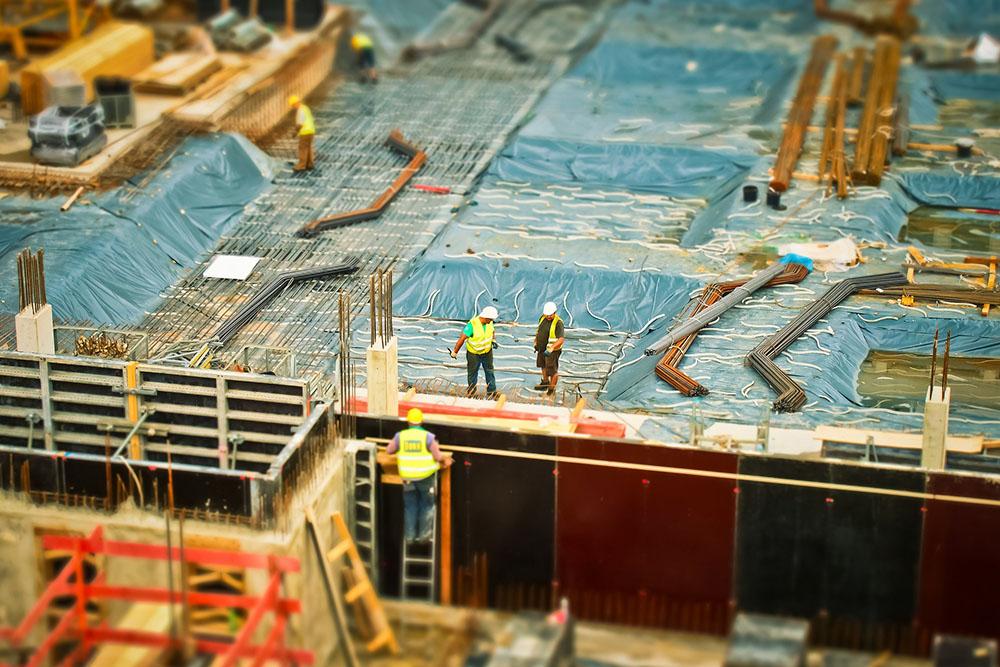 Trabajadores en el tejado de una construcción, con elementos de protección contra los accidentes laborales