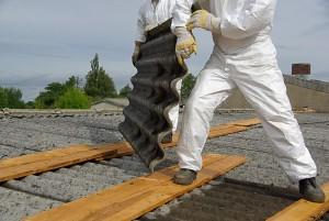 Dos trabajadores desmontando un tejado de uralita bien equipados para no contraer enfermedad profesional