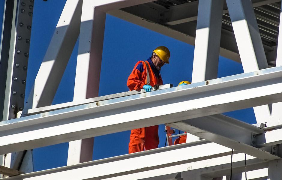 Un obrero en lo alto de una construcción aplicando el plan de accidentes laborales