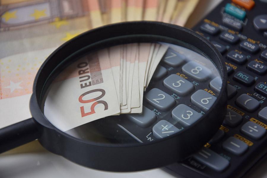 billete, lupa y calculadora, blanqueo de capitales