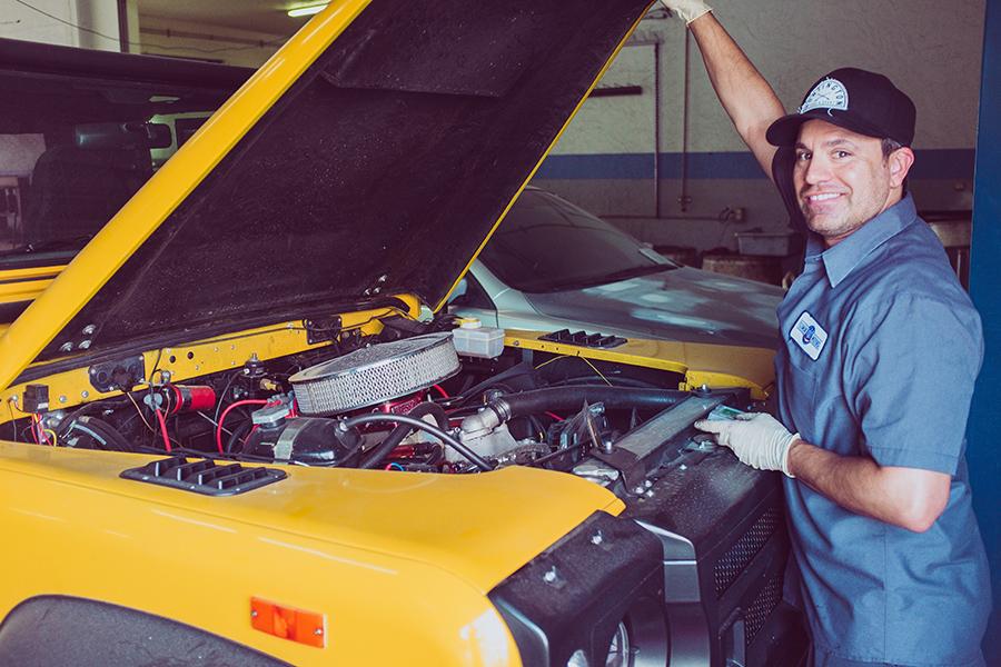 Un mecánico reparando un vehículo teniendo en cuenta los riesgos laborales que contamos en este post de conversia