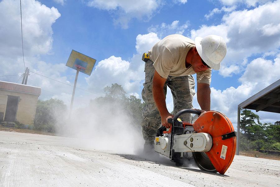 trabajador bien protegido arreglando el suelo