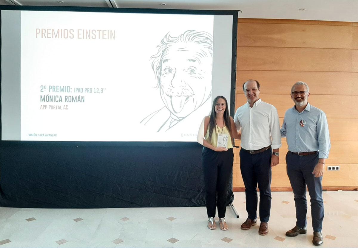 La finalista de los Premios Einstein, Mónica Román, recibe el premio de manos del Consejero Delegado del Grupo HFL, Augusto Carmona, y del Director General de Conversia, Alfonso Corral.